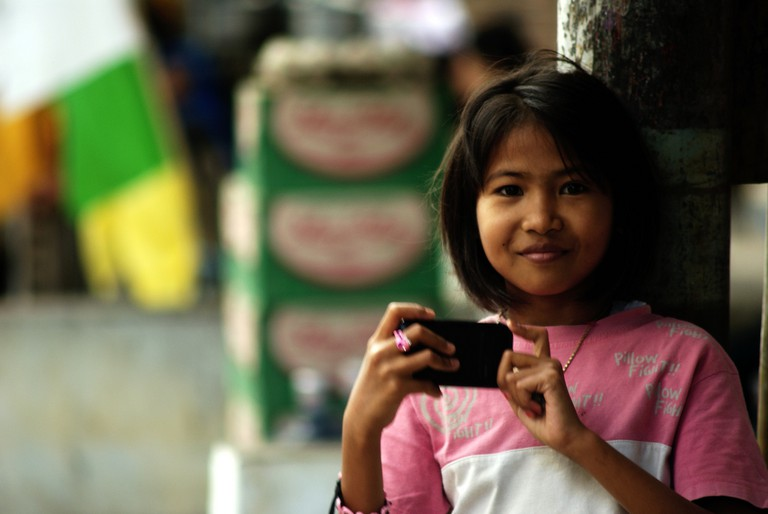A young Indonesian girl with a phone