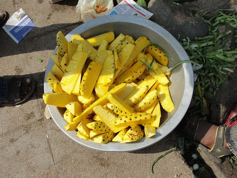 Pineapples are first sliced and then sprinkled and dipped in spices