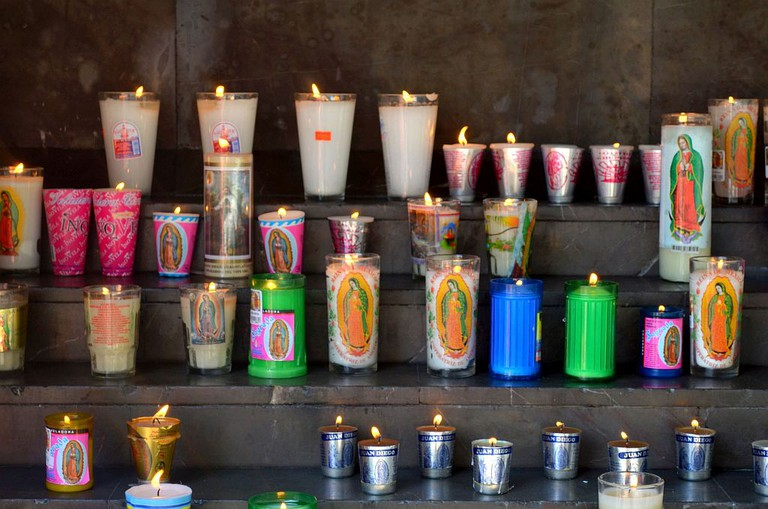 Pilgrims leave offerings and light candles