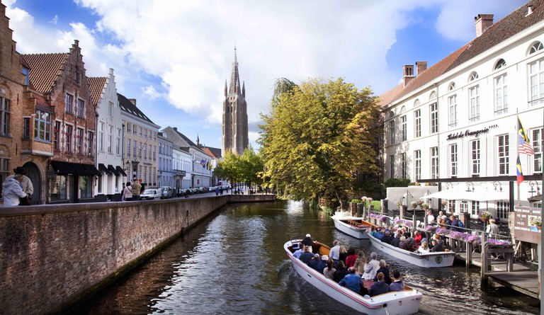 Boats on the Dijver Canal, packed with travelers embracing their tourist status | © Jan D'Hondt / Courtesy of Visit Bruges