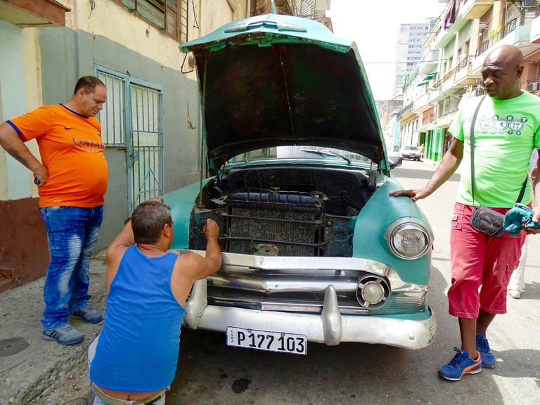 Locals in Havana working on a 1950s American car