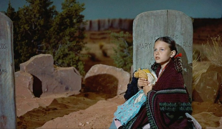 Young Debbie (Lana Wood) hides in vain from the Comanches by her grandmother's grave on the Edwards ranch