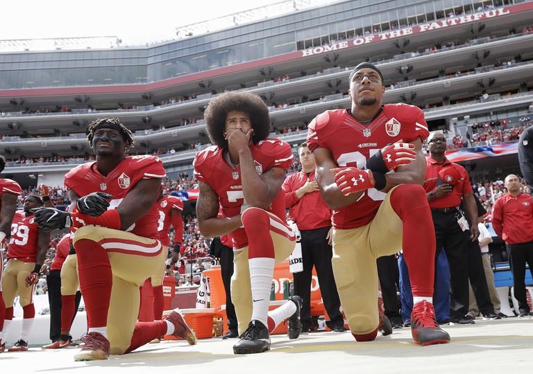 Colin Kaepernick (center) kneels during the national anthem prior to a 2016 NFL game | © Marcio Jose Sanchez/AP/REX/Shutterstock