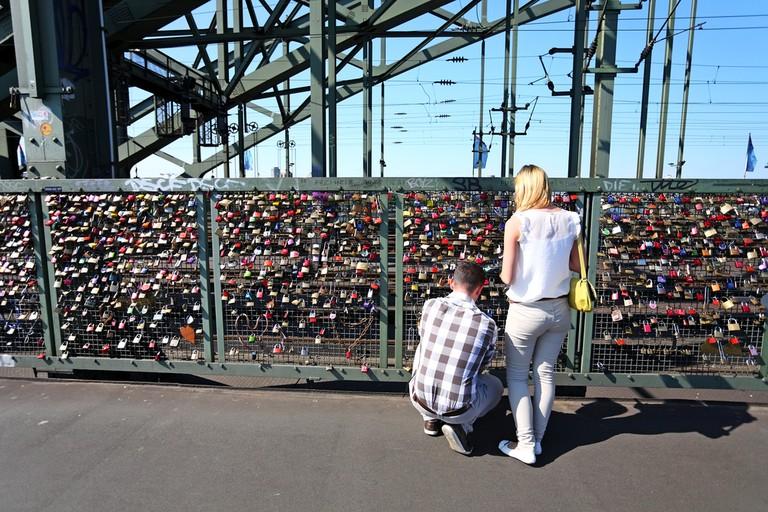 A couple fixes a padlock to the railings of love lock bridge