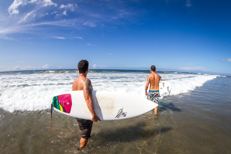 Surfers ready heading out over the black sand of Playa Negra   © LMspencer/Shutterstock