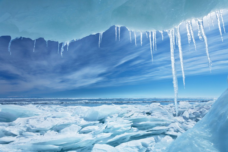 The first drops of icicles on a frozen Lake Baikal