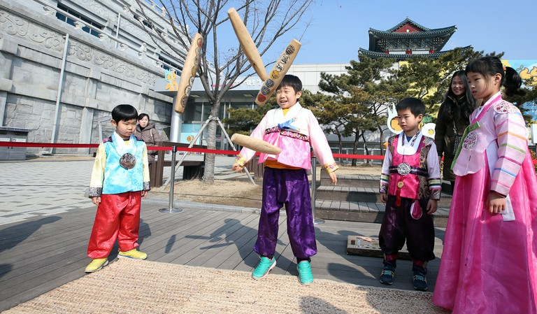 Children playing yut nori, a traditional Korean game, at the National Folk Museum of Korea