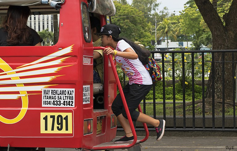 Girl hopping on jeepney