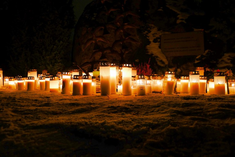 Candles at a graveyard on All Saint's Day / Timo Newton-Syms / Flickr