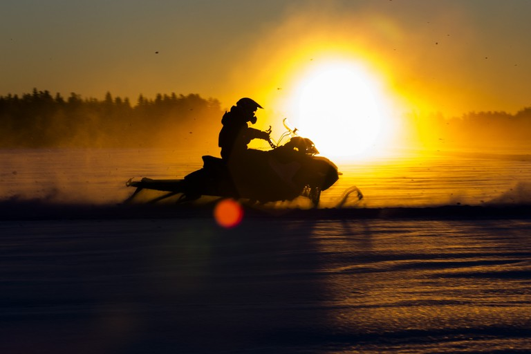 Snowmobile silhouetted against the sunrise / Visit Lakeland / Flickr