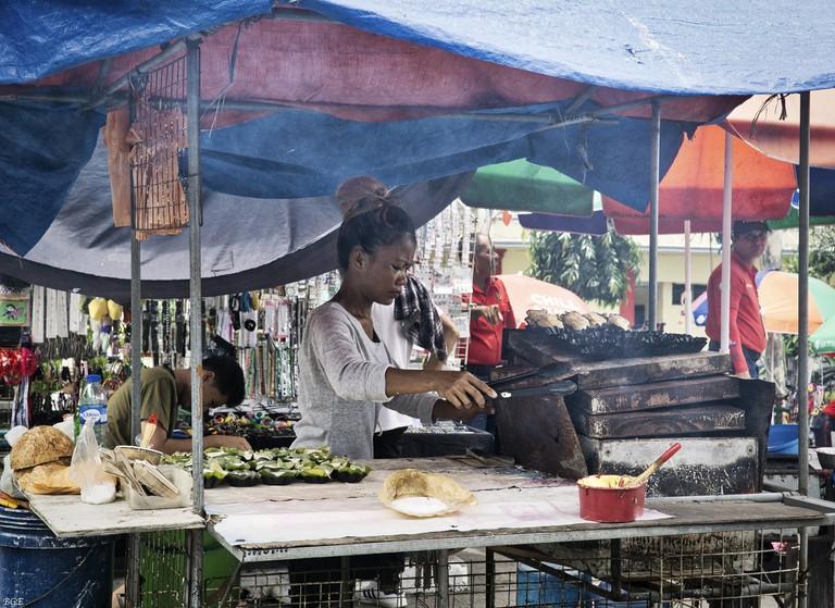 Girl cooking bibingka (a rice cake)