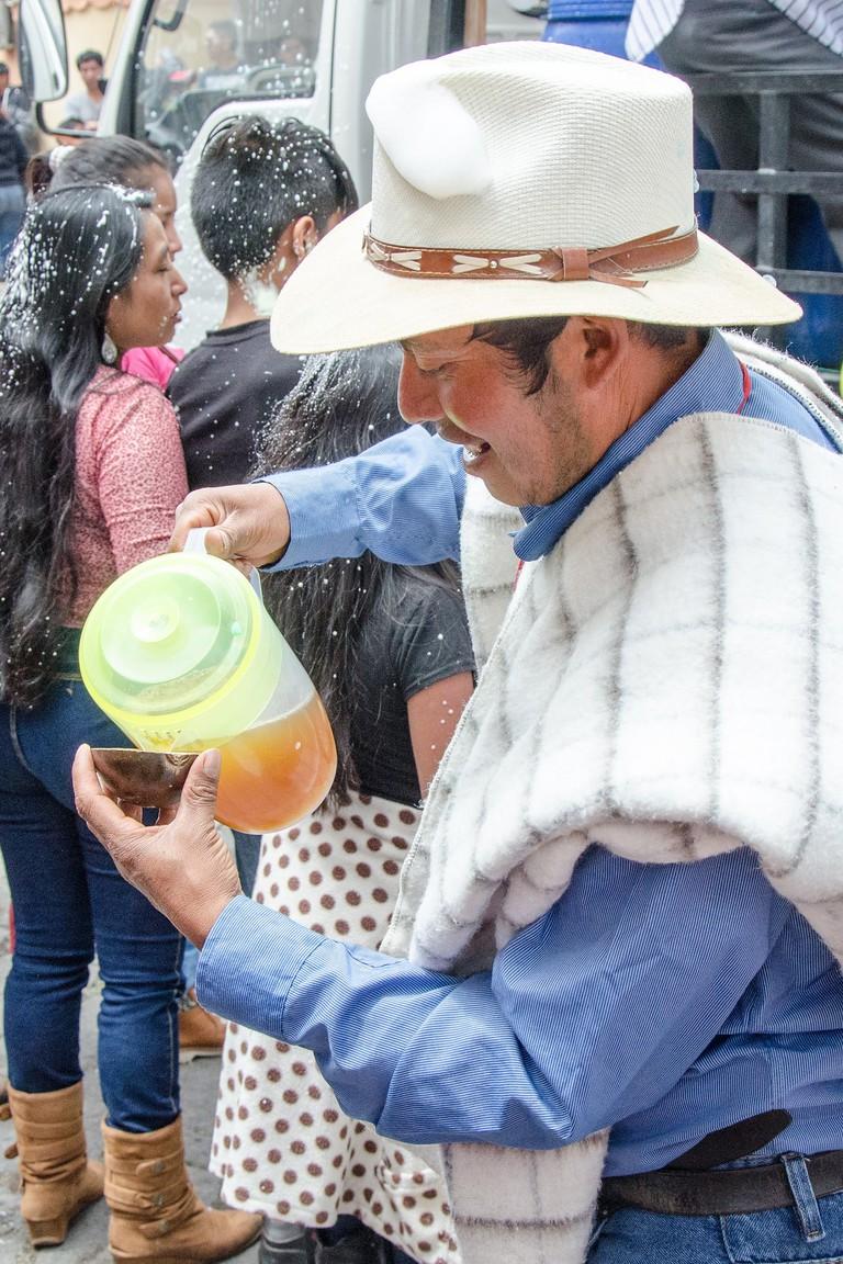 Serving Chicha, Carnival in Guamote, Ecuador