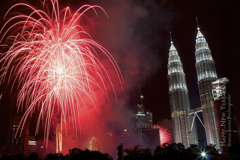 A firework explodes besides the Petronas Towers