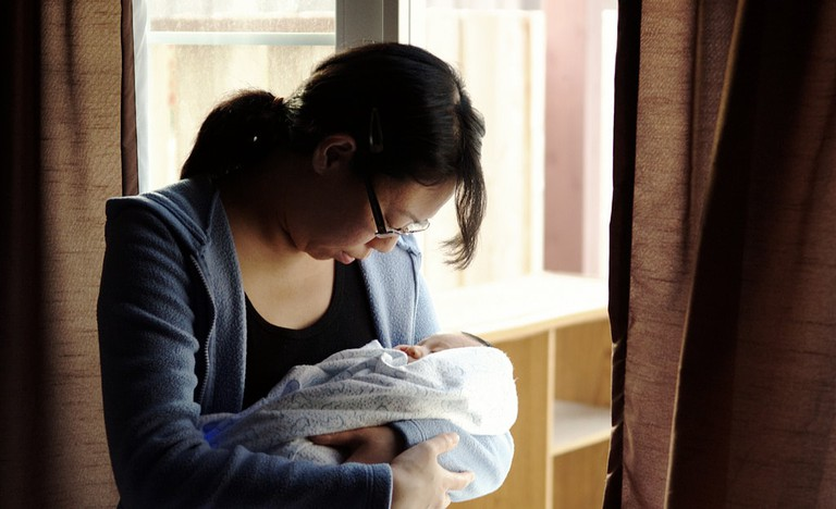 Asian mother cradling her baby