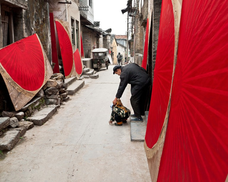 Hand painted fans dry in a narrow street in Fuli, China