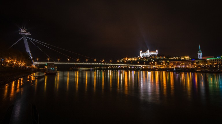 The glittering Bratislava Castle and UFO Tower face each other across the Danube River