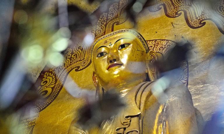 A grand statue of Buddha rests inside Ananda Phaya in Bagan, Myanmar