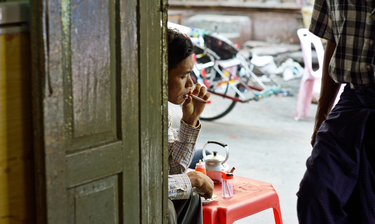 A Burmese man rests at a local shop in Yangon