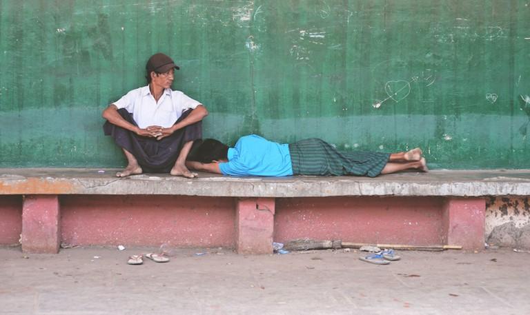 Burmese men dressed in longyis rest at a train stop in Yangon, Myanmar