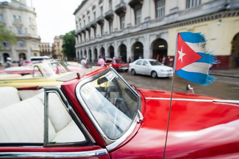 Classic car with Cuban flag