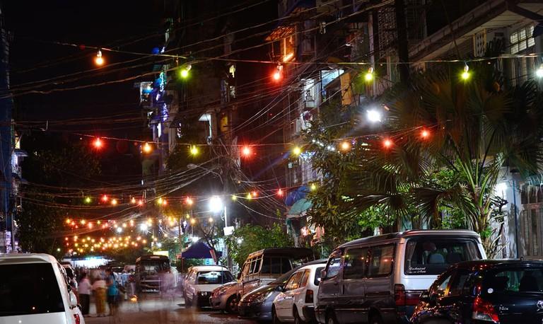Colorful lights hang over a neighborhood street in Yangon
