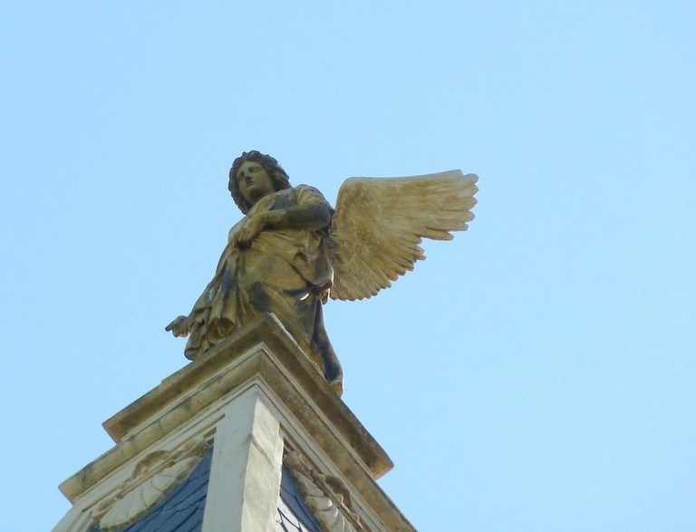 A statue at the top of a church in Barracas