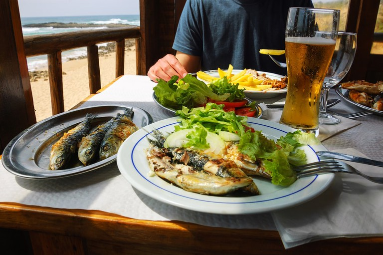 Traditional Portuguese lunch with beach view, Algarve, Portugal   © Elena Dijour/Shutterstock