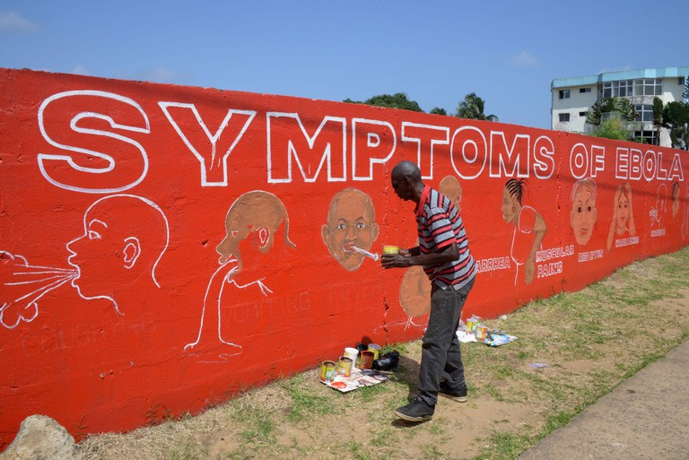 Street artist Stephen Doe paints an educational mural to inform people about the symptoms of the deadly Ebola virus in the Liberian capital Monrovia