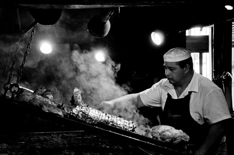 Asador tending the grill in Uruguay, cooking an asado (grilled meats and sausages)