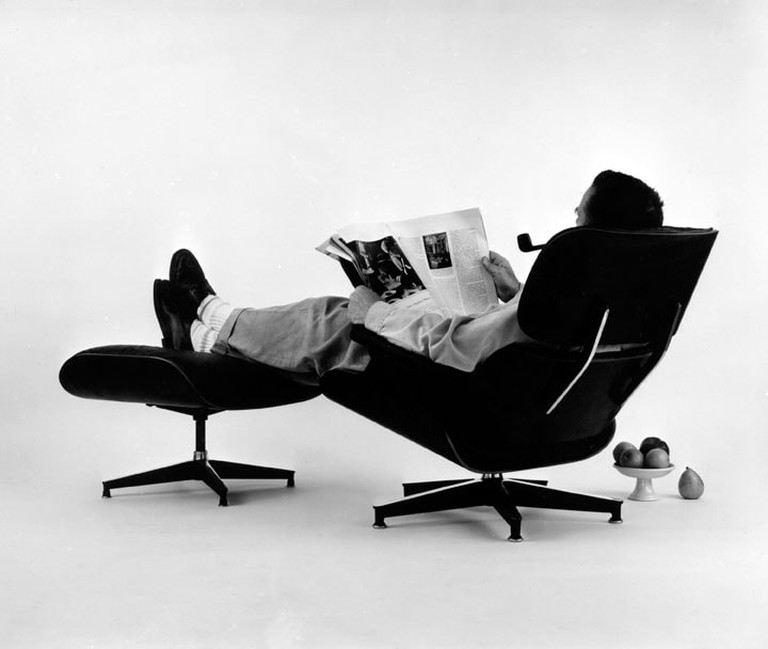 18. An Eames Celebration. Charles Eames in the plywood Lounge and Ottoman, 1956. ∏ Eames Office LLC