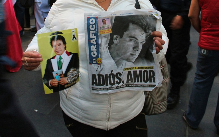 A Juan Gabriel fan holds images of her idol