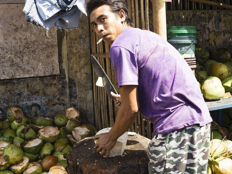 Street vendor preparing a coconut