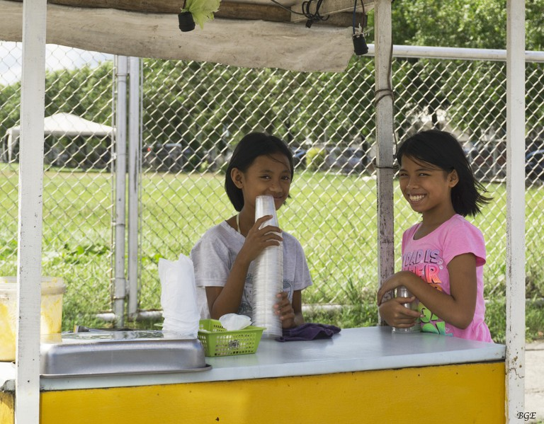 Two young girls manning a drinks stand
