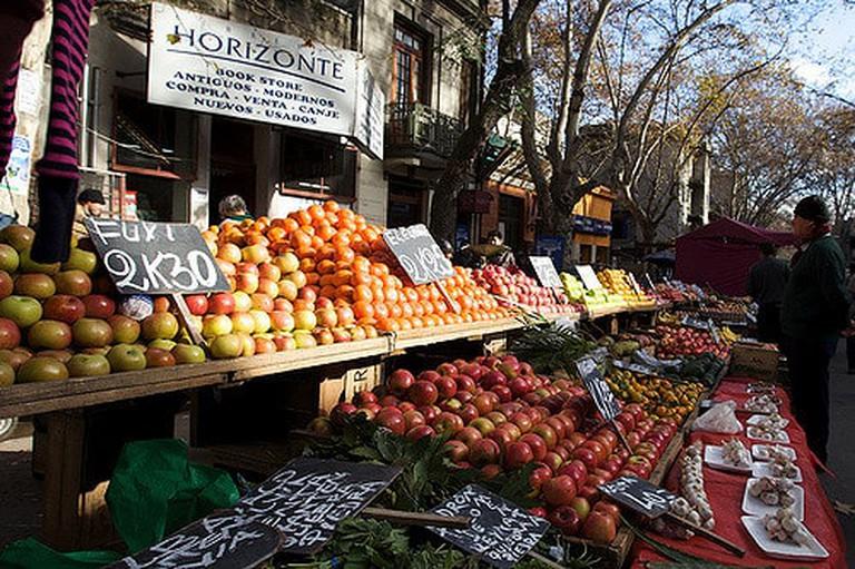 Uruguay street market man looking at some fruit