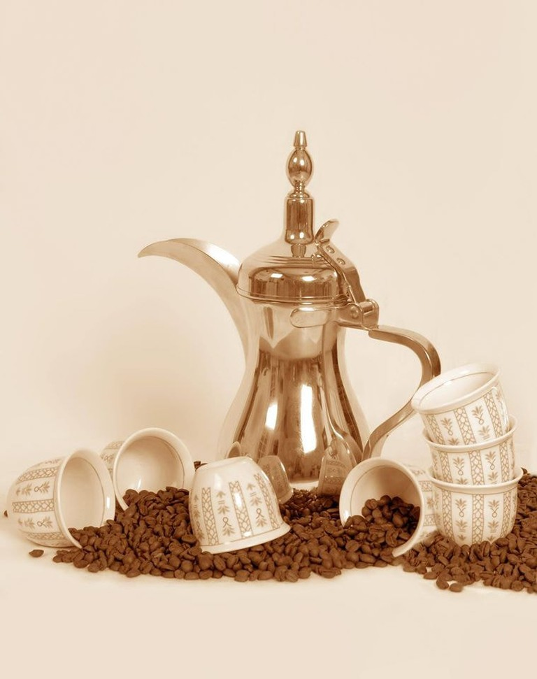 A_dallah_a_traditional_Arabic_coffee_pot_with_cups_and_coffee_beans