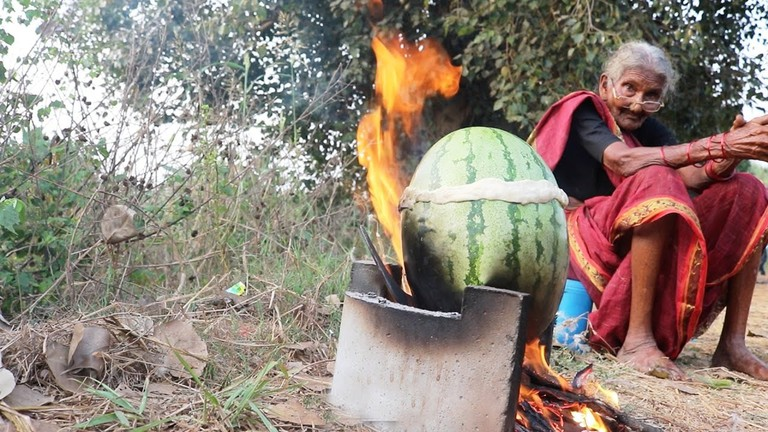 Granny cooking watermelon chicken on open-wood stove