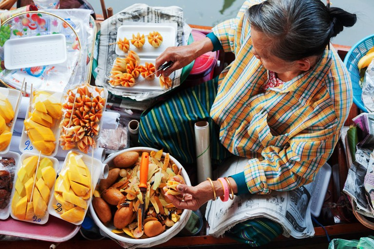Thai woman preparing street food and fruits | © Ivan Mateev/Shutterstock