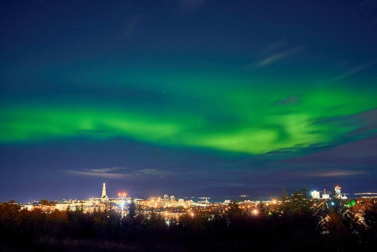 Northern Lights above Reykjavik in Iceland at Night, Iceland   © badahos/Shutterstock