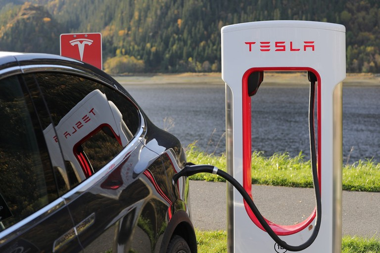 A Tesla Car charging next to a fjord