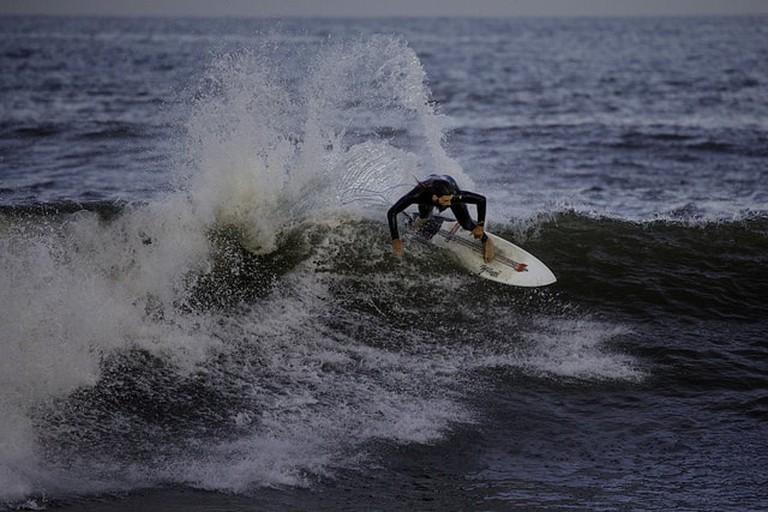 A surfer riding a wave at Punta del Este's Brava Beach