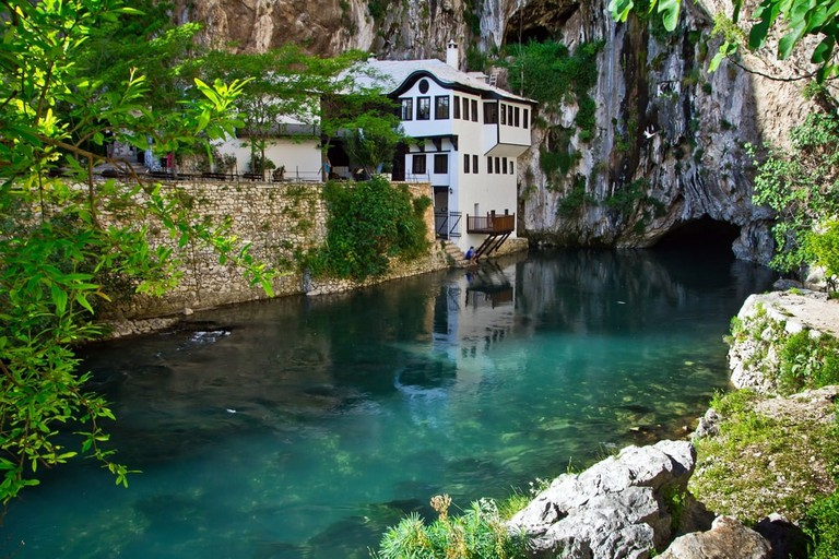 Dervish house on Buna spring with a small waterfall and a cave nearby in a sunny summer day in Blagaj, Bosnia and Herzegovina | © Alex Marakhovets/Shutterstock