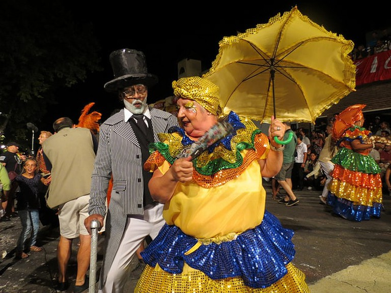 Two performers dressed as an old woman and an old man, dancing together at Carnival in Uruguay