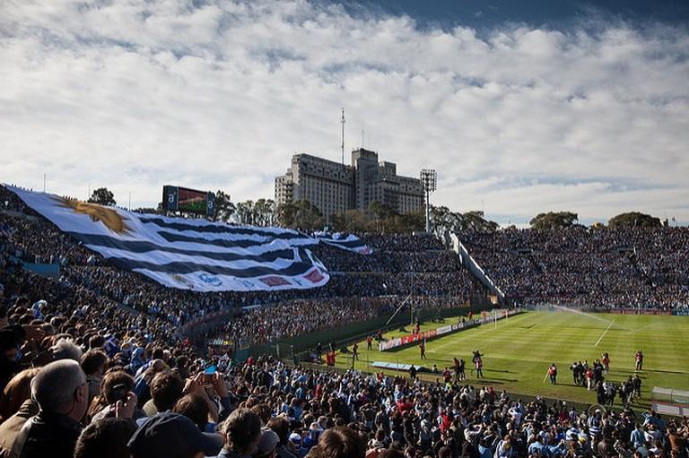 Fans unravel a Uruguayan flag at Uruguay's main Football stadium