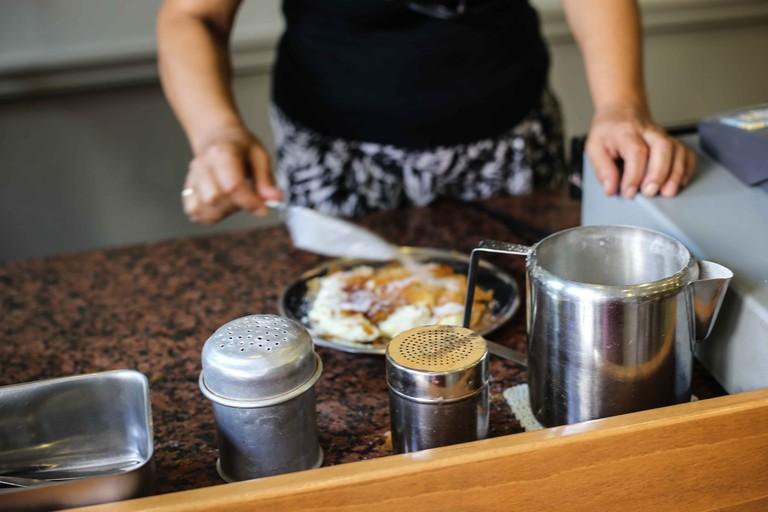Preparing to serve the bougatsa with a coat of sugar and cinnamon | © Eleni Philippou