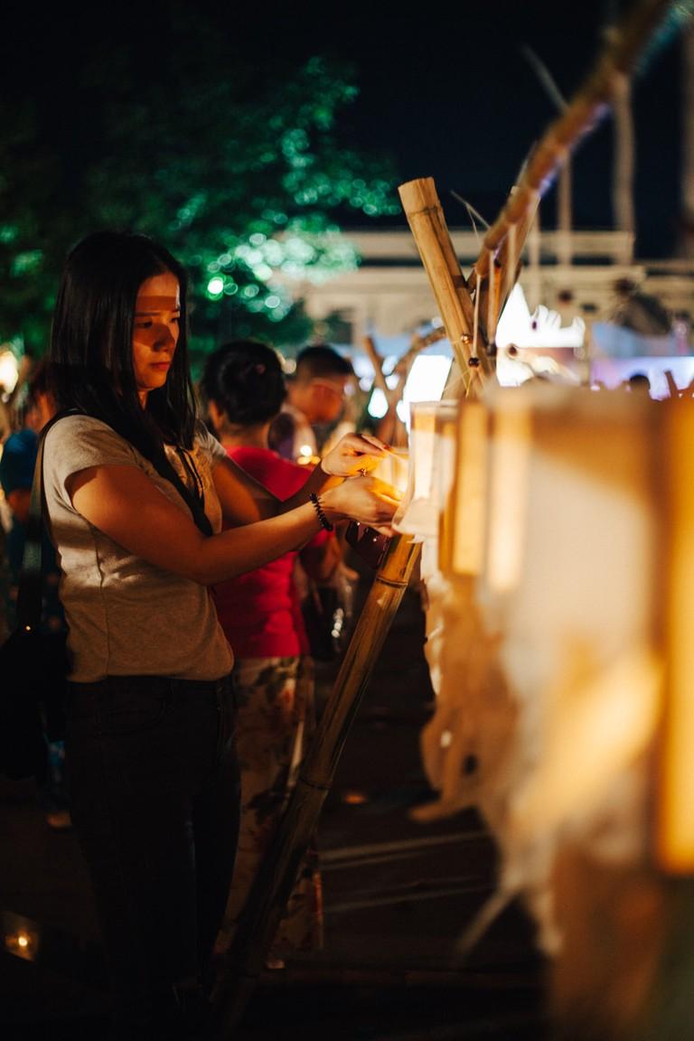 Thai woman lights a lantern at Three Kings Monument | Gioia Emidi / © Culture Trip