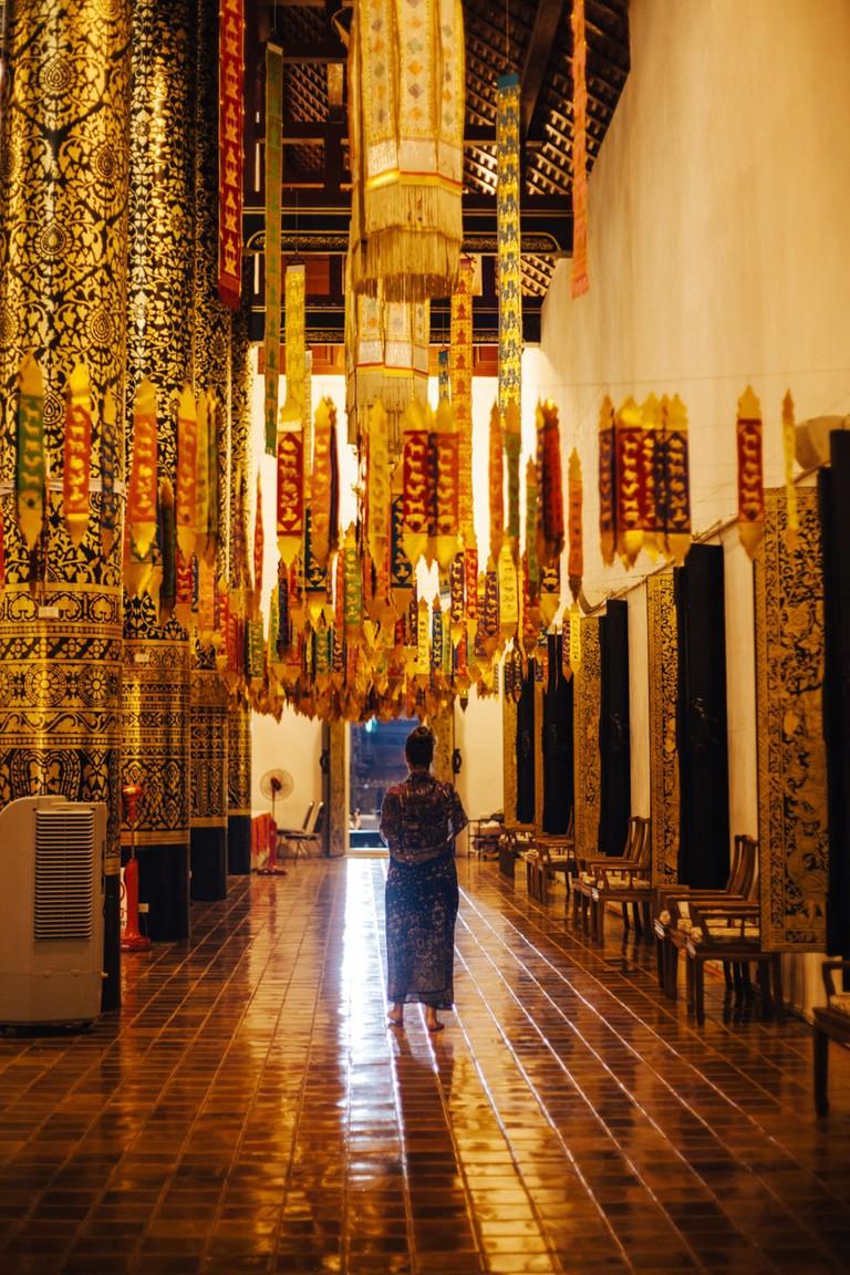 A woman dressed in Lanna clothes walks through a temple | Gioia Emidi / © Culture Trip