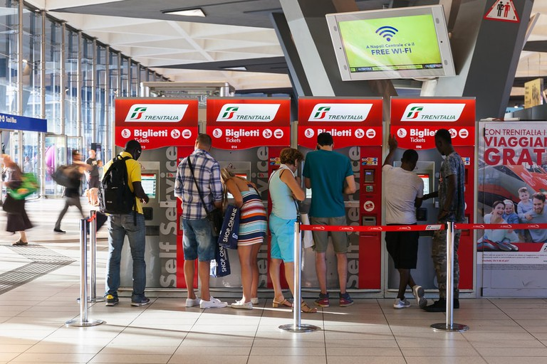 Travellers buying train tickets in Naples, Italy | ©Polifoto/Shutterstock