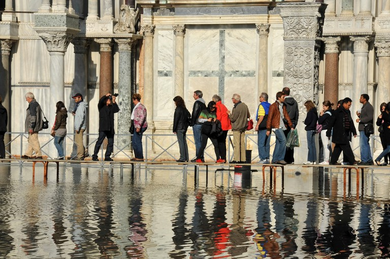 Visitors to Venice walk on duck boards as sea water floods St. Mark's Square, Venice in 2010   Mountainpix/Shutterstock