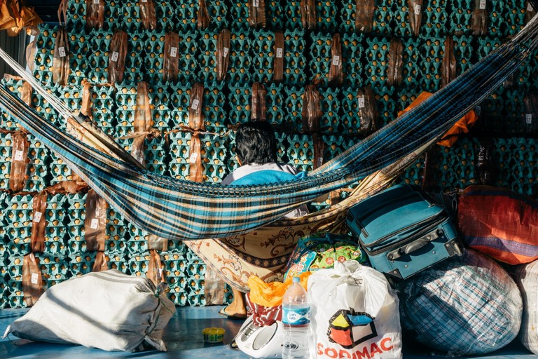 A passenger sits in a hammock strung up in front of the cargo ship's shipment of eggs | Mia Spingola / © Culture Trip