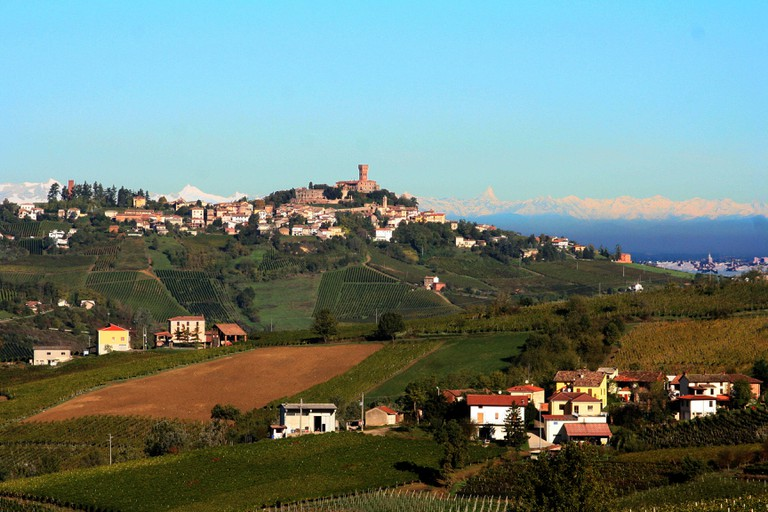 A hill in the wine region Oltrepo Pavese in Milan, with a blue sky, green and brown fields and a village with houses and a castle.
